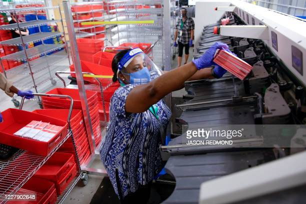 Election worker Truniere Kirby removes ballots from a sorting machine as vote-by-mail ballots for the August 4 Washington state primary are processed...