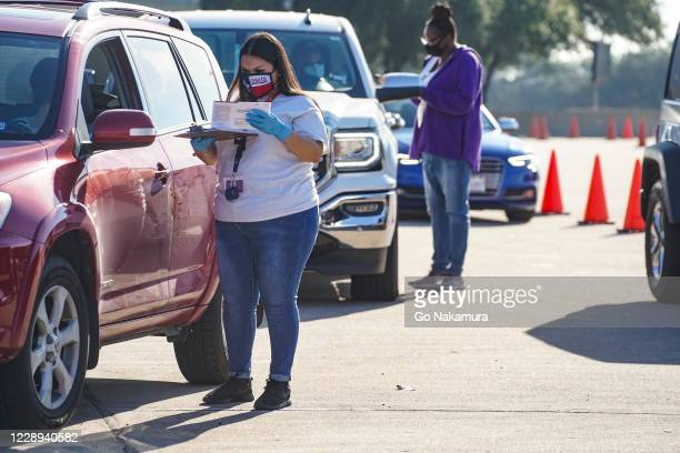 Election workers accept mail in ballot from voters at drive-through mail ballot drop off site at NRG Stadium on October 7, 2020 in Houston, Texas....