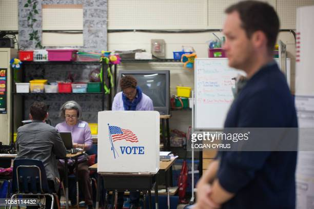 Election workers assist would-be voters at First Ward Creative Arts Academy on November 6, 2018 in Charlotte, North Carolina. - Americans started...