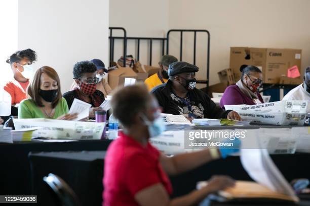 Election workers count Fulton County ballots at State Farm Arena on November 4 2020 in Atlanta Georgia The 2020 presidential race between incumbent...