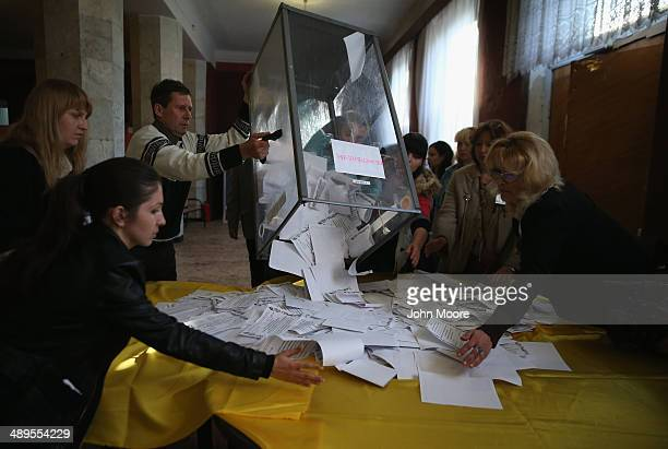 Election workers dump a ballot box to count votes following eastern Ukraine's sovereignty referendum on May 11 2014 in Slovyansk Ukraine ProRussian...