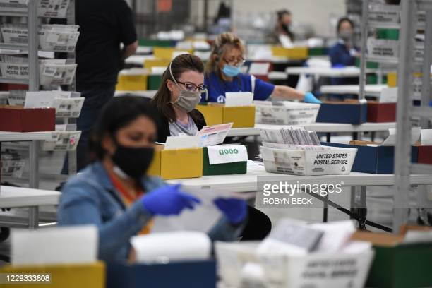 Election workers extract mail-in ballots from their envelopes and examine the ballot for irregularities at the Los Angeles County Registrar...