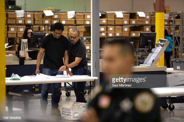 Election workers feed ballots through machines at the Supervisor of Elections Service Center on November 15 2018 in Palm Beach Florida After...