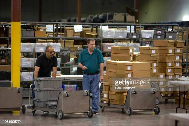Election workers prepare to feed ballots through machines at the Supervisor of Elections Service Center on November 15 2018 in Palm Beach Florida...
