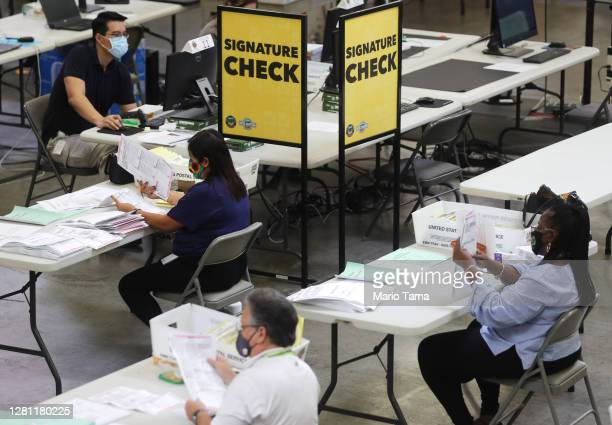 Election workers process mail-in ballots as a monitor displays a livestream of the process at the Orange County Registrar of Voters on October 19,...