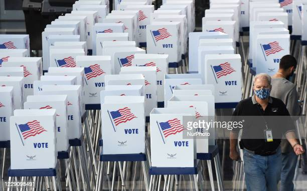 Election workers set up voting booths at an early voting site established by the City of Orlando and the Orlando Magic at the Amway Center, the home...