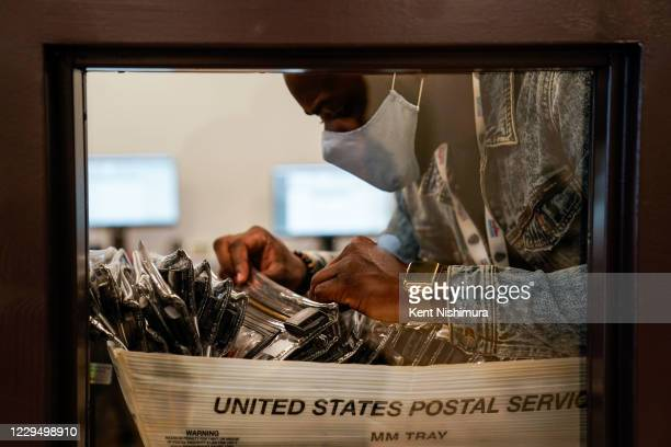 Election workers sort through pouches containing data cards with voting data for transmission at the Gwinnete County Elections Office on Friday, Nov....