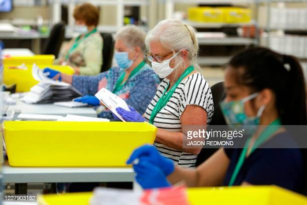 Election workers wear masks and gloves as they open envelopes containing vote-by-mail ballots for the August 4 Washington state primary at King...