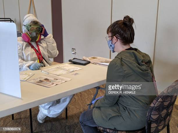 Elections Chief Inspector Mary Magdalen Moser runs a polling location in Kenosha Wisconsin in full hazmat gear as the Wisconsin primary kicks off...