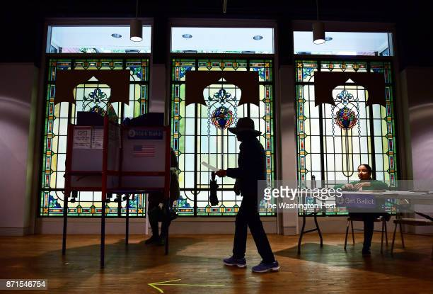 Elections officer Jane Garrido is seen at right as a voter walks in front of windows from Louis Comfort Tiffany Studios while preparing to cast their...
