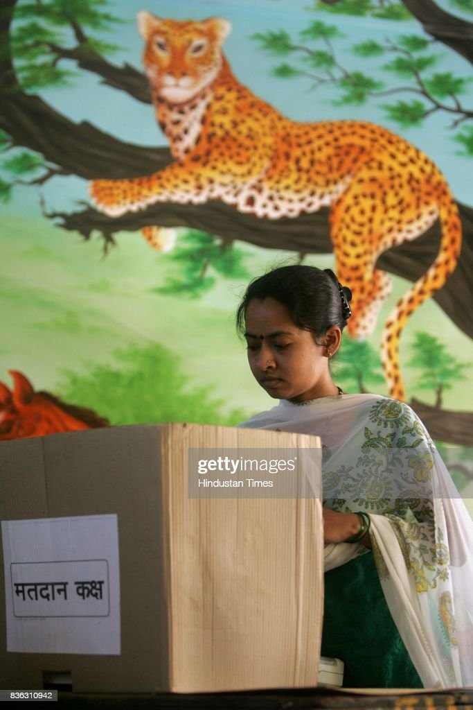 A lady voter casts her vote under watchful eyes for the BMC elections in Malad Kurar Village on Thursday.