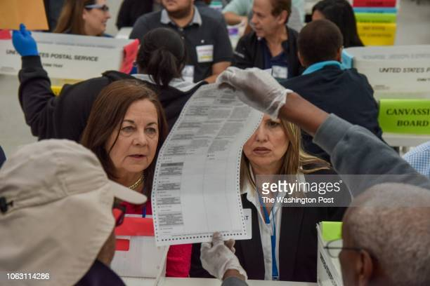 Elections workers and observers go about the work of manually counting votes for Florida's US Senate race at the Broward County Supervisor of...