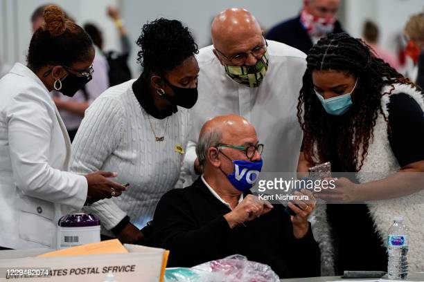 Elections workers gather around and look at their phones at the Detroit Department of Elections Central Counting Board Voting at TCF Center,...