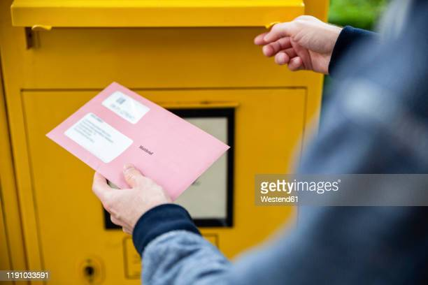 elector holding documtents for the postal vote in front of the mailbox - politische wahl stock-fotos und bilder