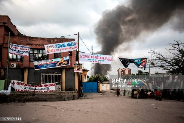 Electoral banners are seen as smoke rises from a fire at the independent national electoral commission's warehouse on December 13 2018 in Kinshasa...