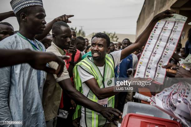 TOPSHOT Electoral commission officers and voters discuss while votes are counted at Shagari Primary School polling station in Yola Adamawa State on...