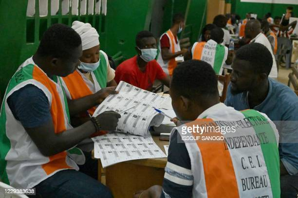 Electoral commission officials check the voter's roll as they count votes at a polling station in Abidjan on October 31 after Ivory Coast's...