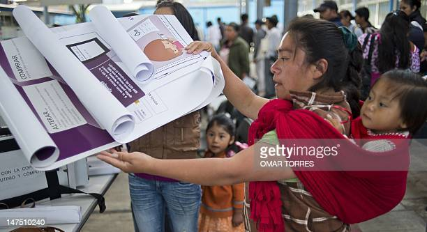 Electoral delegate install posters with instructions to citizens before the opening of a polling station at a school in San Lorenzo Tlacoyucan in...