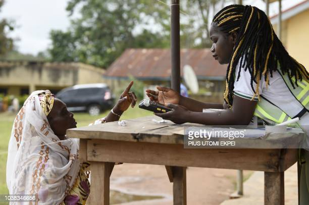 Electoral officer tries to capture finger prints of a voter with a card reader during the Osun State gubernatorial election in Ede in the Osun State...