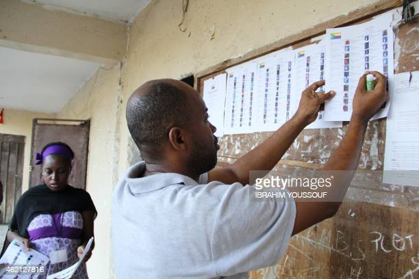 Electoral officers from Comoros paste candidates list on the wall of a voting station as polls open in the Comoros legislative elections on January...