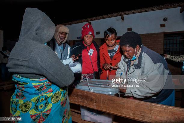 Electoral officials and political party monitors close ballot boxes at the end of voting during the presidential elections during the presidential...