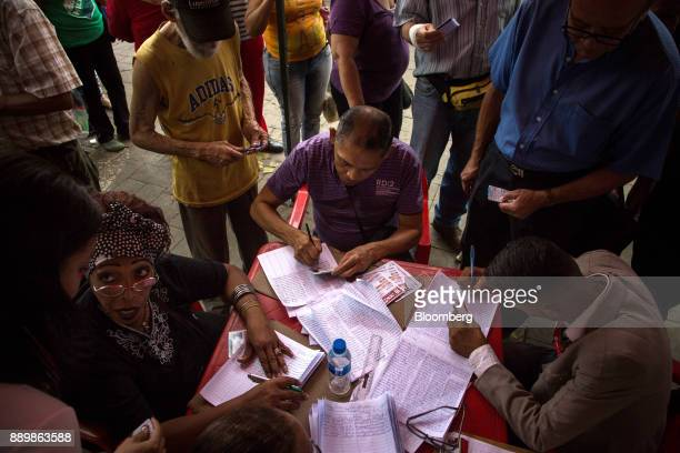 Electoral officials check government issued 'Carnet de La Patria' electronic identity cards outside a polling station during a nationwide mayoral...