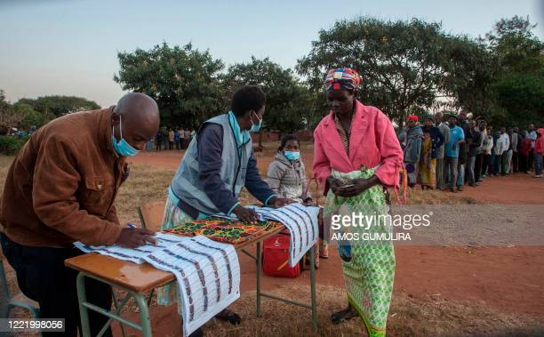 Electoral officials check the voters roll while people queue to vote at the Malembo polling station during the presidential elections in Lilongwe on...