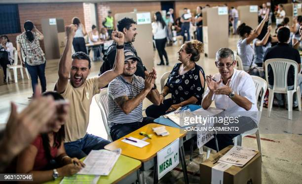 Electoral officials cheer after closing the polls during the first round of the presidential election on May 27 in Medellin Antioquia department...
