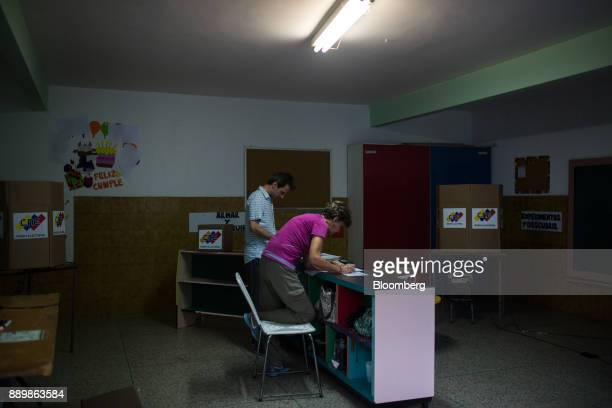 Electoral officials wait for voters inside a polling station during a nationwide mayoral election in Caracas Venezuela on Sunday Dec 10 2017 Major...