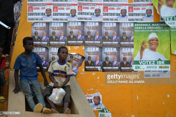 Electoral posters are seen plastered on a wall as Malian incumbent president Ibrahim Boubacar Keita arrives at the Gao stadium on July 18 2018 for a...