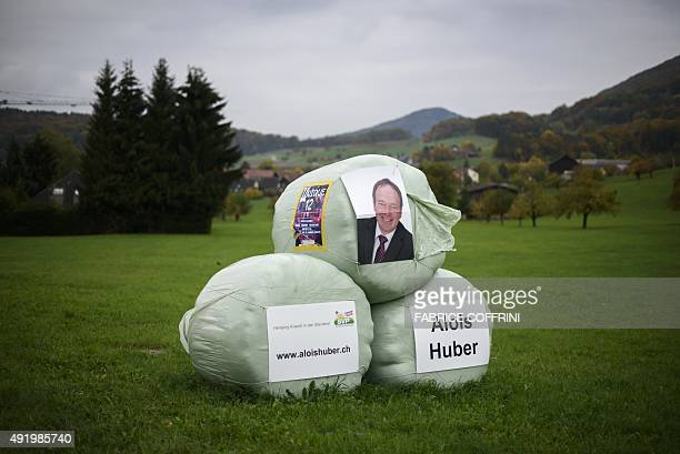 Electoral posters of Alois Huber candidate of the Swiss People's Party for the Swiss National Council are seen on haystacks at the entrance of the...