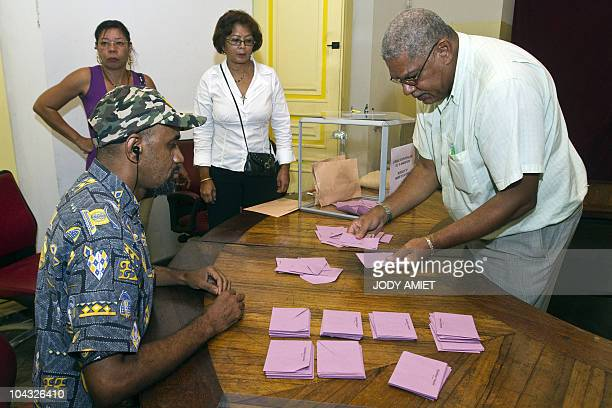 Electoral workers count ballots in the polling station of Cayenne on the French South American territory of Guiana on January 10 for the referendum...