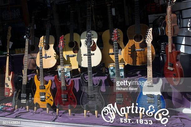 Electric and acoustic guitars on display in Martin Co one of the last music shops to stay in Denmark Street in London's famous Tin Pan Alley a result...