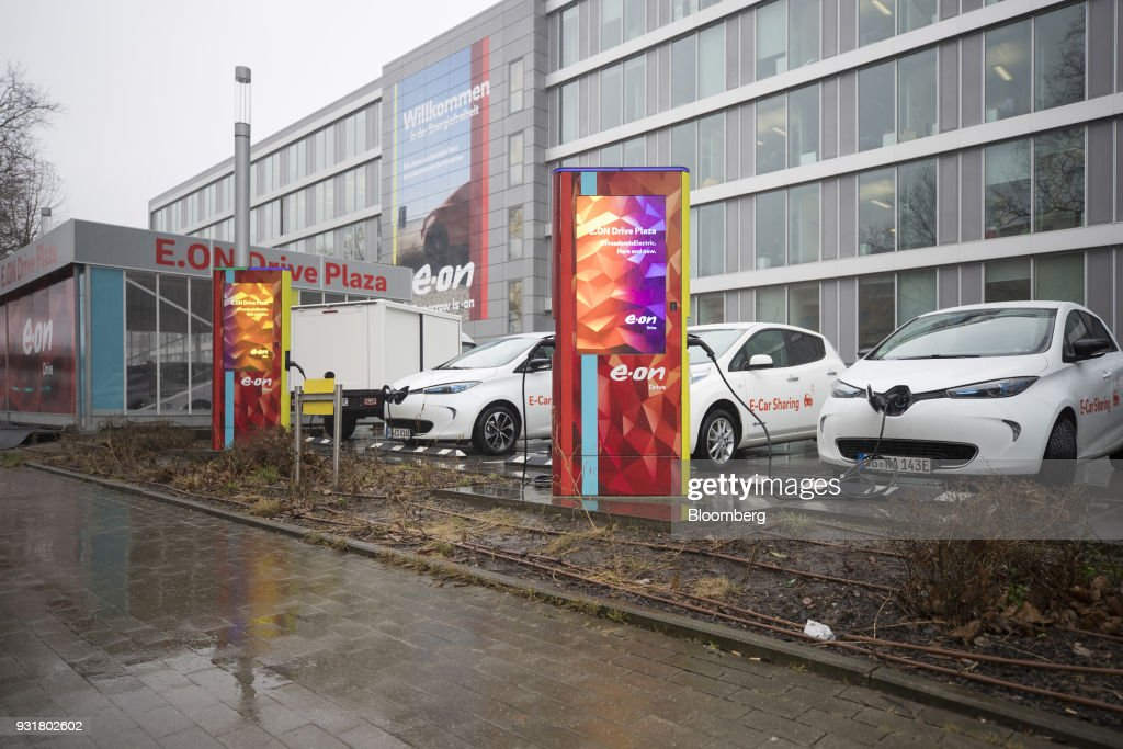 Electric automobiles sit at charging stations outside the headquarters of EON SE in Essen, Germany, on Tuesday, March 13, 2018. EON will shed as many as 5,000 jobs in the deal to take over Innogy SE, a move that marks the biggest shakeup in Germany's energy business in years. Photographer: Jasper Juinen/Bloomberg via Getty Images