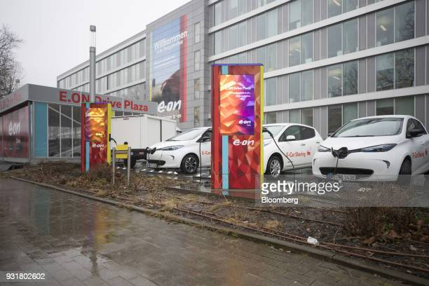 Electric automobiles sit at charging stations outside the headquarters of EON SE in Essen Germany on Tuesday March 13 2018 EON will shed as many as...