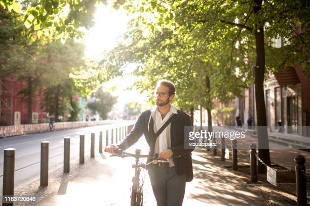 electric bike commuter walking with his bike - alternative fuel vehicle stock pictures, royalty-free photos & images