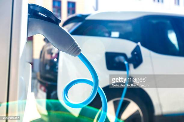 electric car at charging station - electric vehicle charging station stock photos and pictures