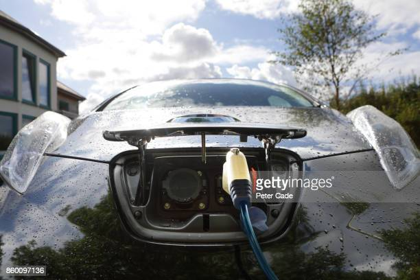 electric car being charged outside home - electric car stock pictures, royalty-free photos & images