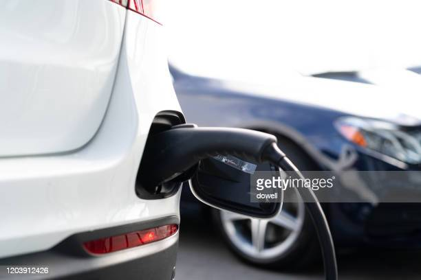 electric car being charged - attaccante foto e immagini stock