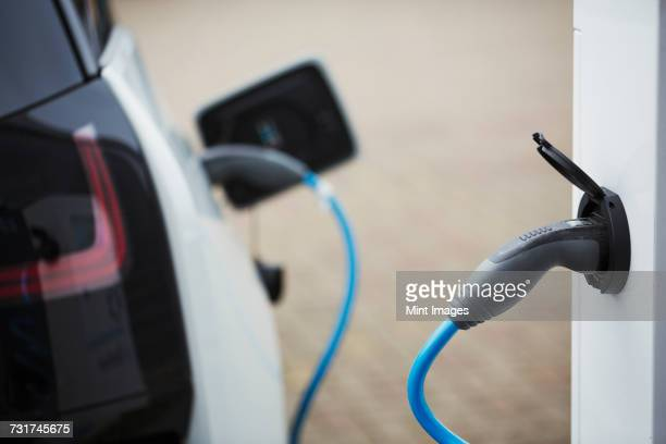 Electric car being charged with a cable connected to a wall socket.