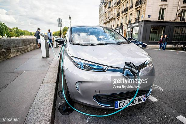 electric car charging on paris street, france - renault stock pictures, royalty-free photos & images