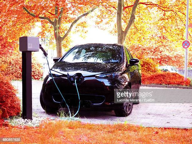 electric car charging on road against autumn trees - elektroauto stock-fotos und bilder
