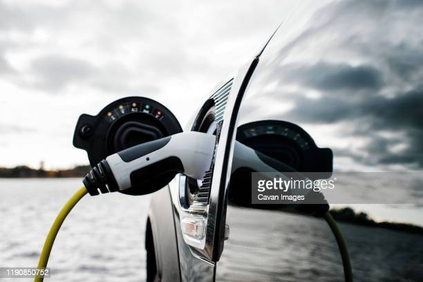 electric car charging socket and lead by the beach - electric car stock pictures, royalty-free photos & images