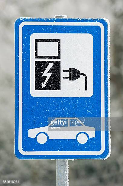 Electric car charging station sign at car park in the snow in winter Belgium