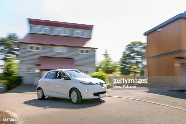 Electric car driving through neighbourhood