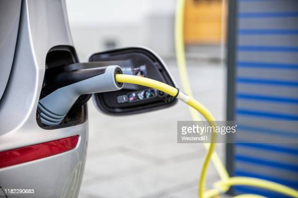 electric car gettig charged at an charging station - elektronik industrie stock-fotos und bilder
