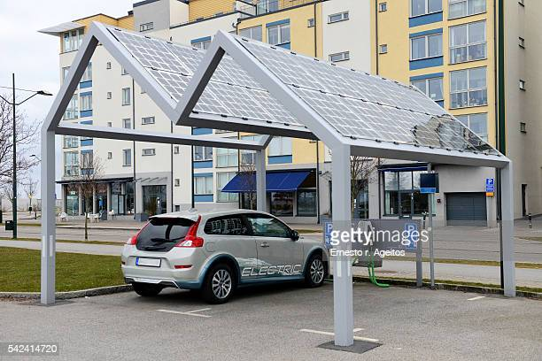 electric car on solar power station - electric vehicle charging station stock photos and pictures