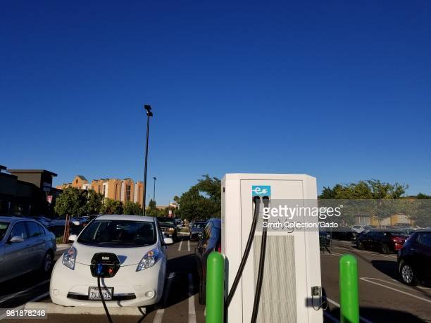 Electric car plugged in and charging at an eVgo electric vehicle charging station in a parking lot in Dublin California June 20 2018