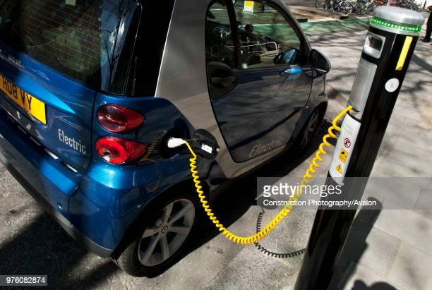 Electric car receiving a charge from a special allocated city parking bay Central London UK