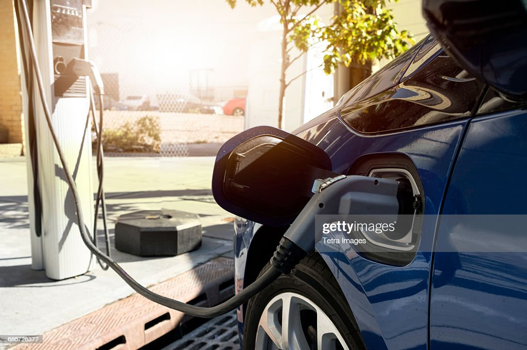 Electric car recharging in charging station : Stock Photo